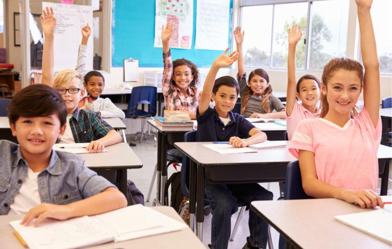 kids in school, raising their hands